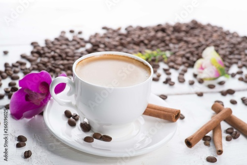Café en grains white cup of coffee on a background of scattered coffee beans on a white background