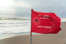 Red Flag With Swimming Warning Waving In The Wind On The Beach