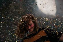 A Girl Dancing Under A Confetti Rain At A Festival