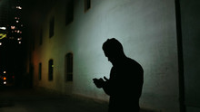 Silhouetted Man Checking His Phone