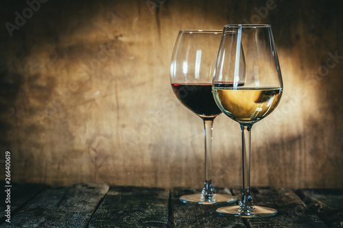 Poster Wine Red and white wine in glasses on rustic background, copy space