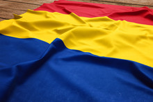 Flag Of Romania On A Wooden Desk Background. Silk Romanian Flag Top View.