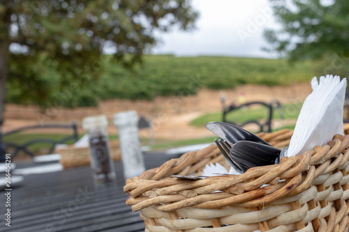 Stickers pour portes Pique-nique basket with cutlery in foreground, out of focus farm landscape