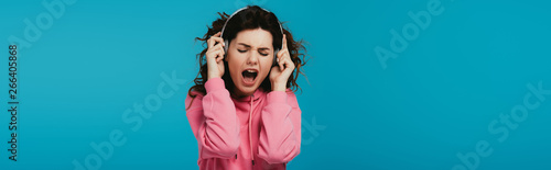 panoramic shot of attractive curly woman singing while listening music in headph Wallpaper Mural