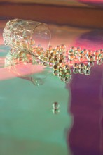 Transparent Vitamin Capsules Fail From Glass On Colorful Holographic Background