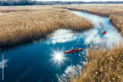 Group of people in kayaks among reeds on the autumn river. Fototapet