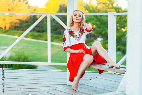 Fototapety, obrazy: Gorgeous young blonde woman with makeup, curly hairstyle in stylish red white dress posing on bench in garden arbor. sitting and looking at camera and smile. outdoor shot in the park at summer daytime