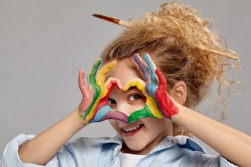 Prekrasna djevojčica s oslikanim prstima pozira na sivoj pozadini.