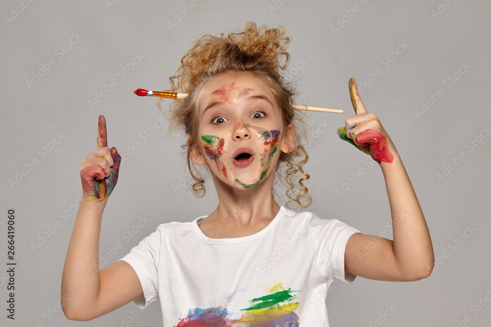 Fototapety, obrazy: Beautiful little girl with a painted fingers is posing on a gray background.
