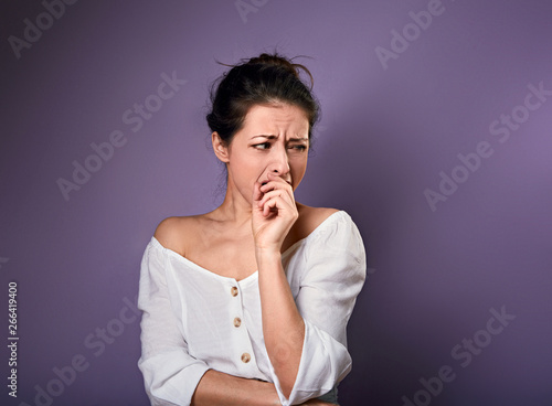 Fototapeta Beautiful unhappy woman in white shirt looking with disgust and cover mouth the