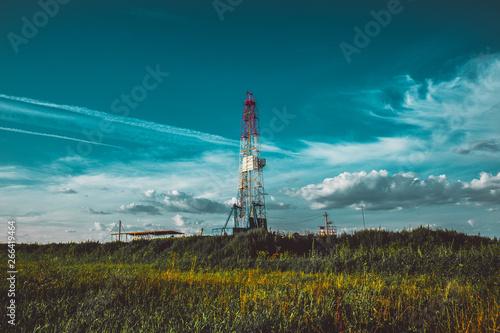 Fototapeta Land oil drilling rig in a green field obraz