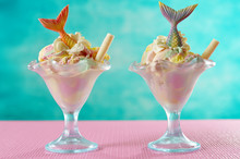 Mermaid Sea Theme Rainbow Ice Cream Sundaes With Mermaid Tails And Candy Shells And Turtles, On Pink And Blue Background.