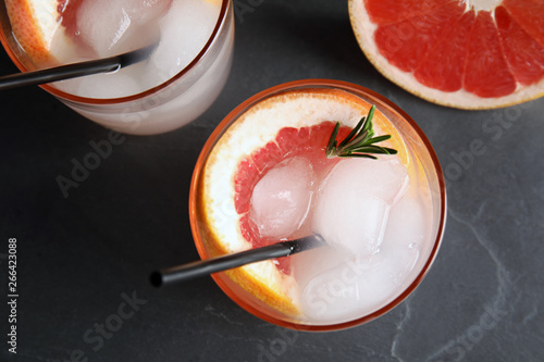 Fototapeta Glasses of cocktail and grapefruit slice on dark table, flat lay obraz na płótnie