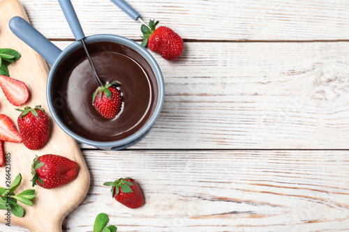 Chocolate fondue with strawberries and marshmallow on wooden table