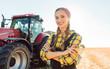 Leinwandbild Motiv Stolze Landfrau steht vor Landmaschinen auf dem Acker