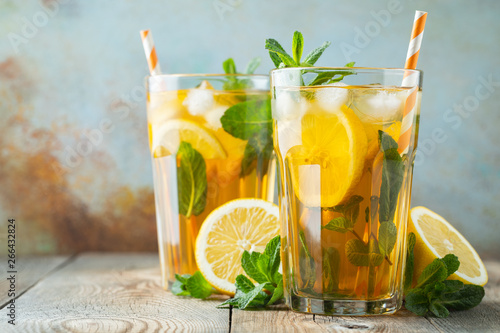 Fotografia  Traditional iced tea with lemon and ice in tall glasses on a wooden rustic table