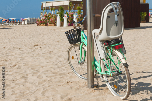 Fotografie, Obraz  bicycle with child chair stands on pillar on the beach on sunny day