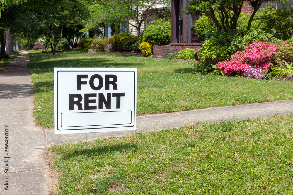 Fototapeta FOR RENT sign posted in lawn advertising home for rent.
