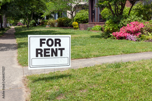 Fotografie, Obraz FOR RENT sign posted in lawn advertising home for rent.
