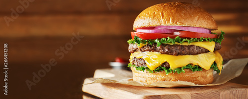 Fototapeta double cheeseburger with lettuce, tomato, onion, and melted american cheese with panoramic composition obraz