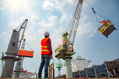 Photo  stevedore or foreman, engineering, loading master talks to crane driver by walki