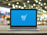 Fototapeta Panels - Shopping cart flat icon with modern laptop computer on wooden table over blur light and shadow of shopping mall, Business shop online concept