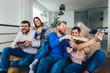 Leinwandbild Motiv Group of friends play video games together at home, having fun.