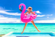 canvas print picture - Summer vacation fun funny woman jumping with flamingo swimming pool float around waist excited of tropical hotel holiday.