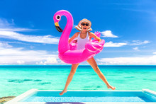Summer Vacation Fun Funny Woman Jumping With Flamingo Swimming Pool Float Around Waist Excited Of Tropical Hotel Holiday.