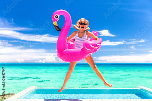 Photo Summer vacation fun funny woman jumping with flamingo swimming pool float around waist excited of tropical hotel holiday