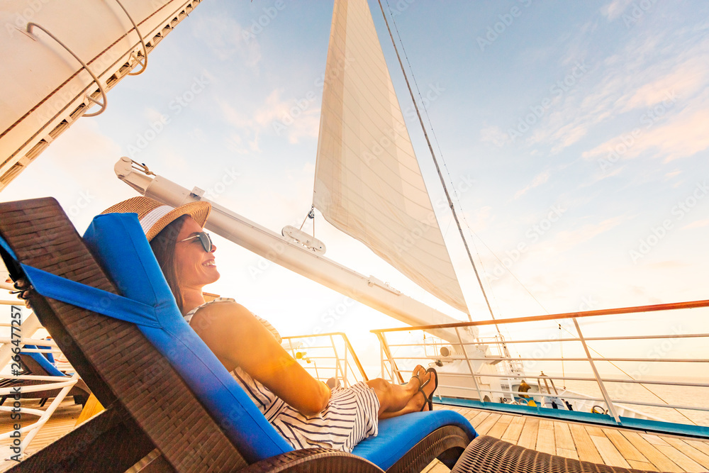 Fototapety, obrazy: Luxury cruise vacation woman relaxing in lounger chair enjoying sunset on yacht deck with sail in wind sailing in getaway destination summer travel lifestyle.