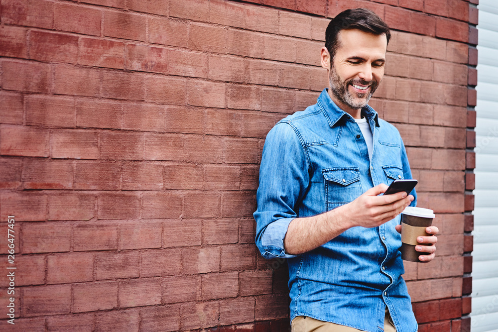 Fototapeta Cheerful man leaning against wall in the city using smartphone and having coffee