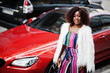 Fashionable african american woman in pink striped jumpsuit with fluffy faux fur coat posed against rich red luxury car with mobile phone at hand.