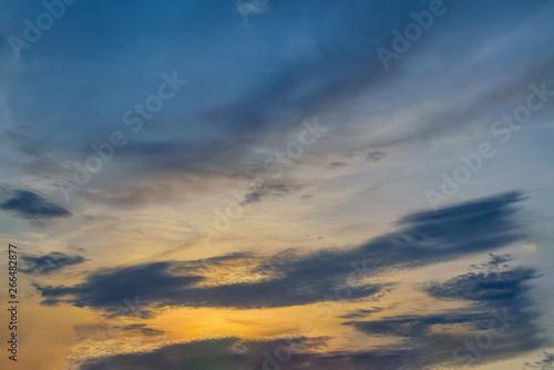 Fototapeta Blue sky with gold clouds - dramatic sunset, beautiful natural background. Setting sun illuminates the clouds. obraz na płótnie