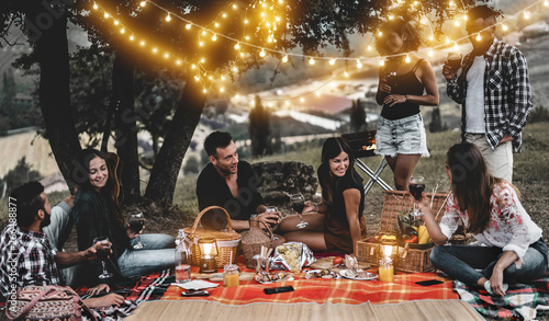 Tuinposter Wijngaard Happy friends having fun at bbq dinner with vintage lights outdoor drinking wine - Young people celebrating on weekend summer night - Friendship, party and youth concept - Focus on center couple