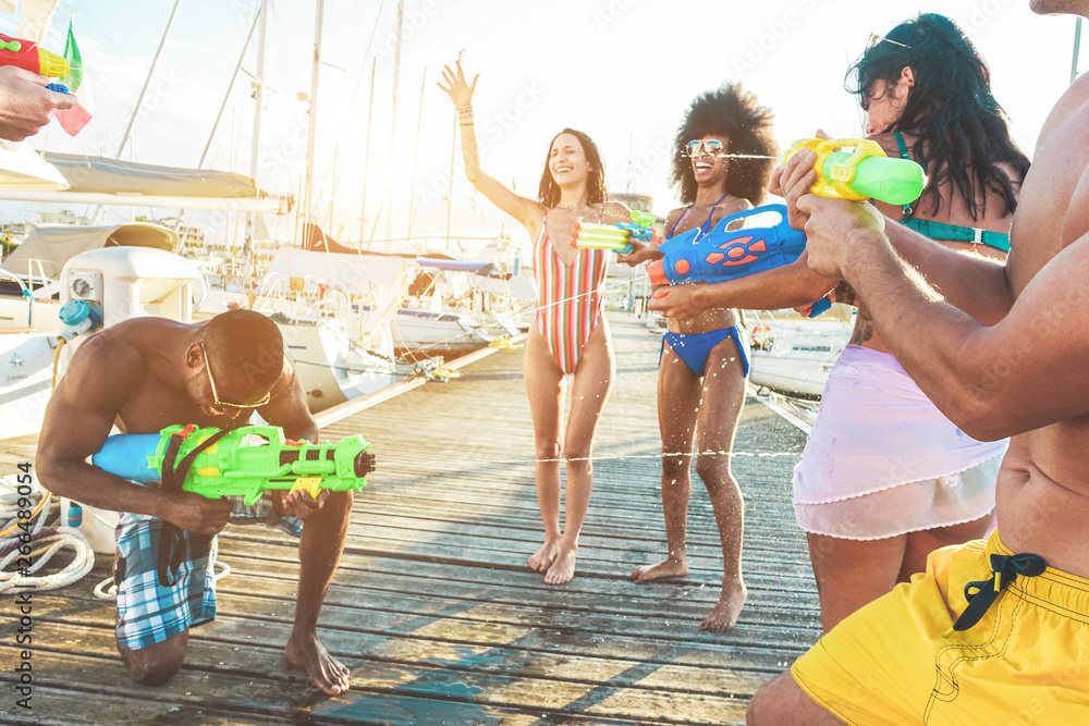 Fototapeta Happy friends doing battle party with water guns - Young millennials people laughing and having fum in summer vacation - Youth lifestyle and holiday concept - Focus on right man hand