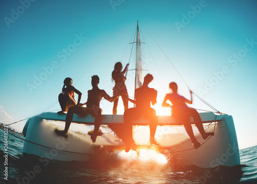 Leinwand Poster Silhouette of young friends chilling in catamaran boat - Group of people making