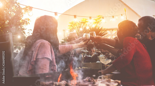 Photo  Happy trendy family cheering with red wine at barbecue dinner outdoor - Differen