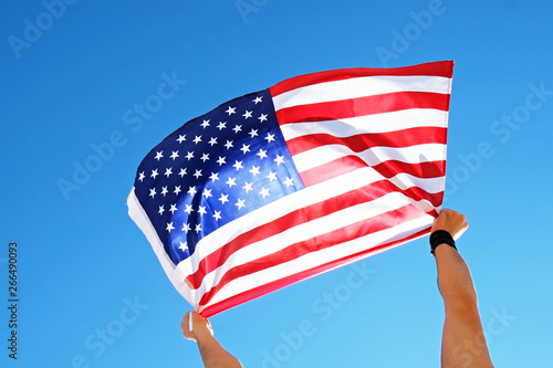 Photo  Close up shot of man hands holding United State of America flag waving on the wind, clear blue sky