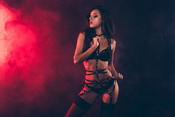 Portrait of lovely magnificent stunning gorgeous charming adorable attractive sporty wavy-haired lady wearing tightening swordbelt teasing isolated over black red light background