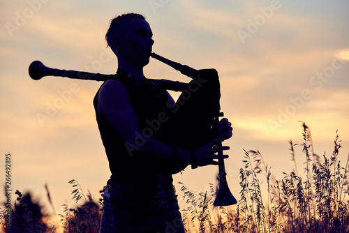 Leinwand Poster A young modern man plays musical bagpipes outside. Siluet