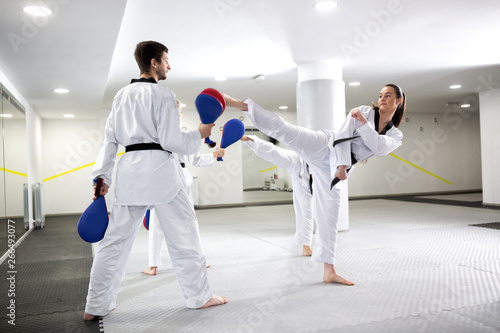 Photo Martial arts competitors and their trainers practicing high kicks in taekwondo