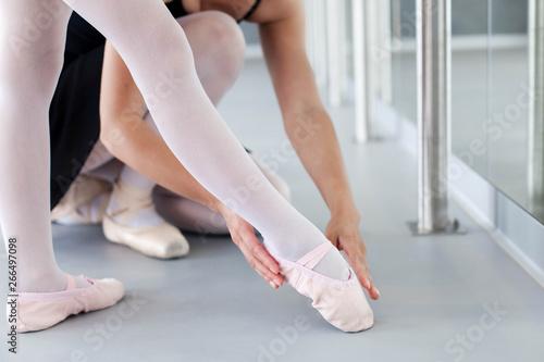 Foto Little ballerina and ballet teacher in classical dancing school
