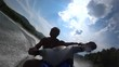 muscular guy rides on the river on a jet ski. riding a jet ski on a mountain river. blue sky with clouds, water splashes and turns on jet ski. front view from the first person. stock video footage.