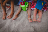 kids play with toys on beach, family feet in sand