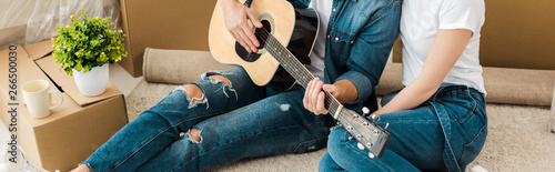 Panoramic shot of man sitting on carpet with wife and playing acoustic guitar - 266500030