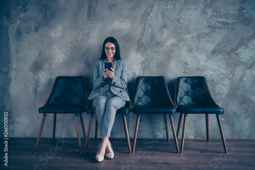 Full length body size photo beautiful she her business lady hands arms telephone look screen wait call office interview read news sit comfort office chair wear specs formal wear checkered plaid suit