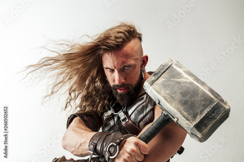 Leinwanddruck Bild - master1305 : God of thunder. Blonde long hair and muscular male model in leather viking's costume with the big hammer cosplaying Thor isolated on white studio background. Fantasy warrior, antique battle concept.