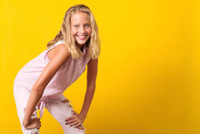 Cute Pre-teen Girl Wearing Fashion Summer Clothes Posing On Yellow Background. 10 Years Old Girl With Beauty Eyes, Blonde Hairl And White Teeth Smile. Kid Urban Style, Pre Teen Summer Fashion.
