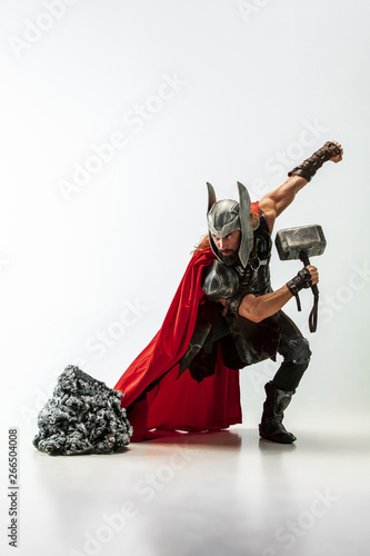Photo  Long hair and muscular male model in leather viking's costume with the big hammer cosplaying Thor isolated on white studio background